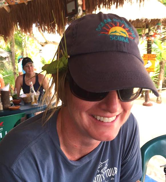 CozInfo owner woman at beach-side bar, wearing baseball hat with grasshopper toy made from palm leaves.
