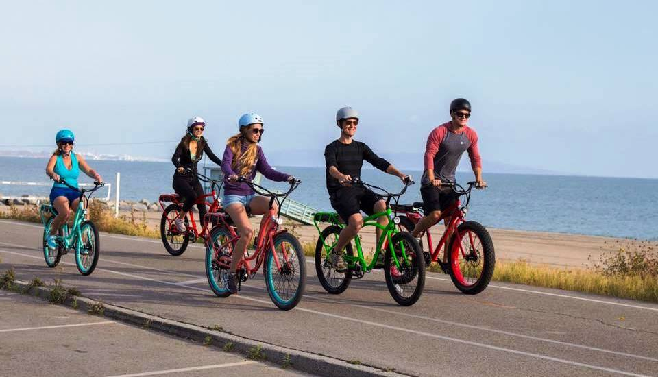 Electric bike tour group with guide on coastal road
