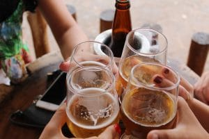 """4 beer glasses clinking in """"cheers"""" at outdoor bar"""