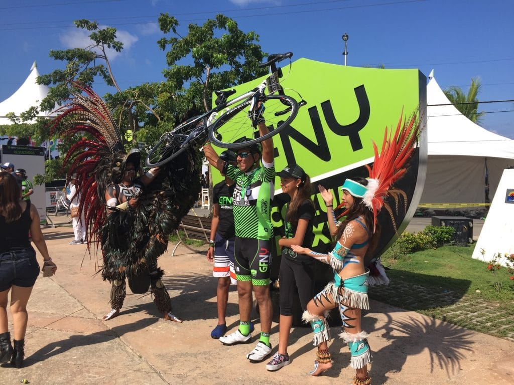 image of bike racer at finish line with performers in Mayan garb