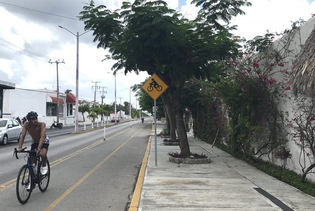 Bicyclist and bike lane on side of main road in Cozumel