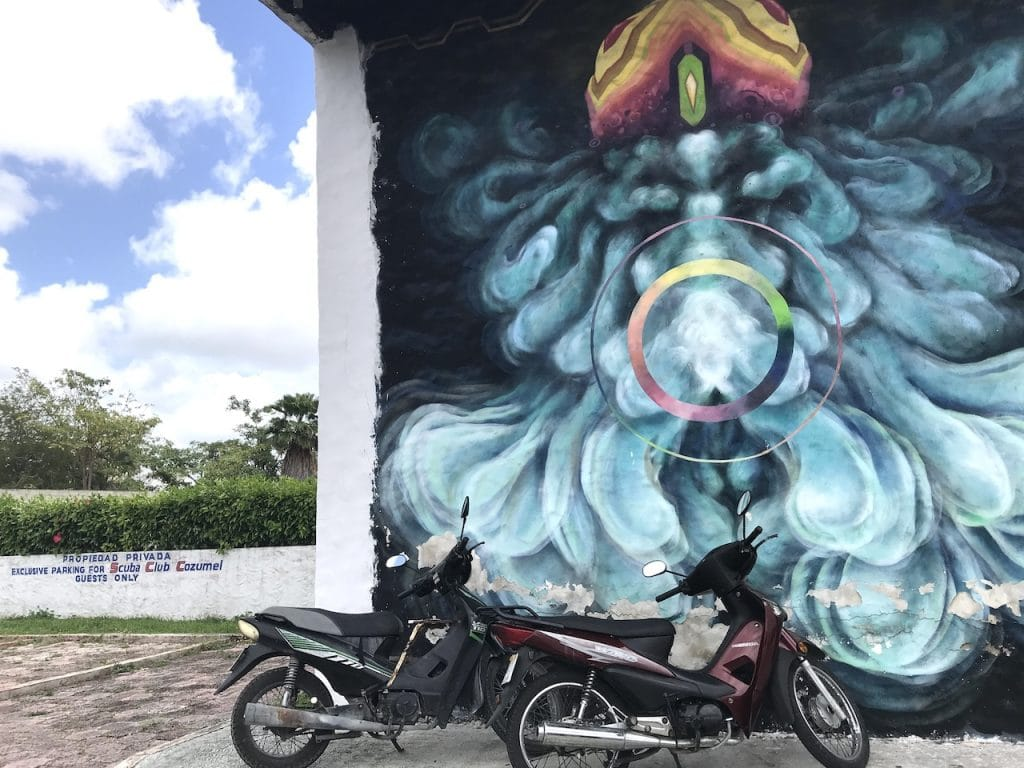 A few motos parked in front of cool streen mural