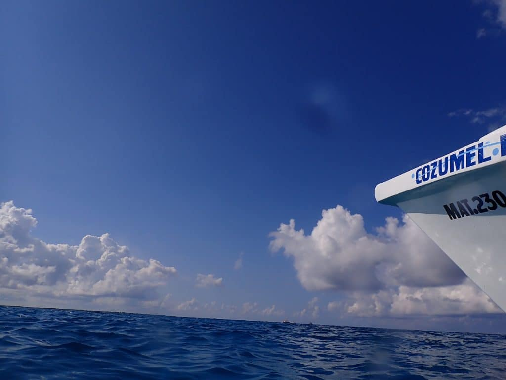 """Cozumel """"Bubbles"""" boat in the marine park with blue water and blue sky"""