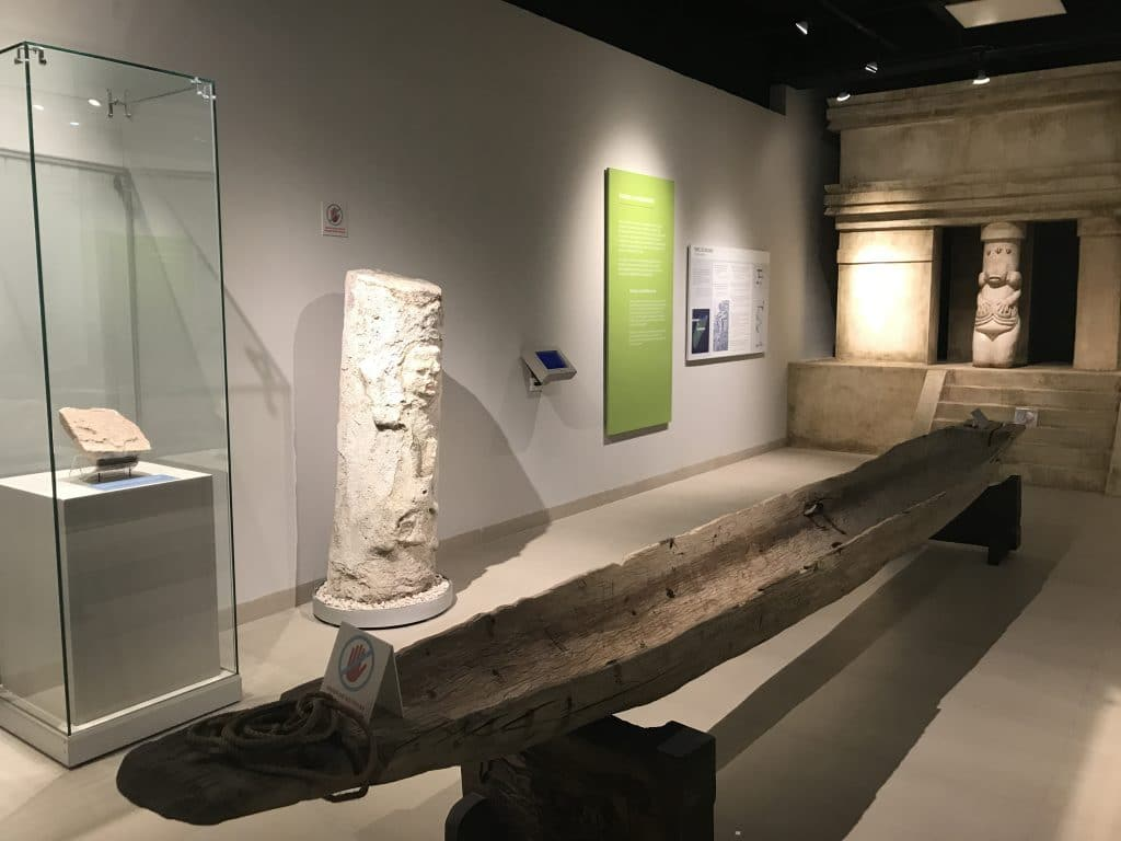 Cozumel museum gallery with ancient stellae and a wooden Mayan canoe
