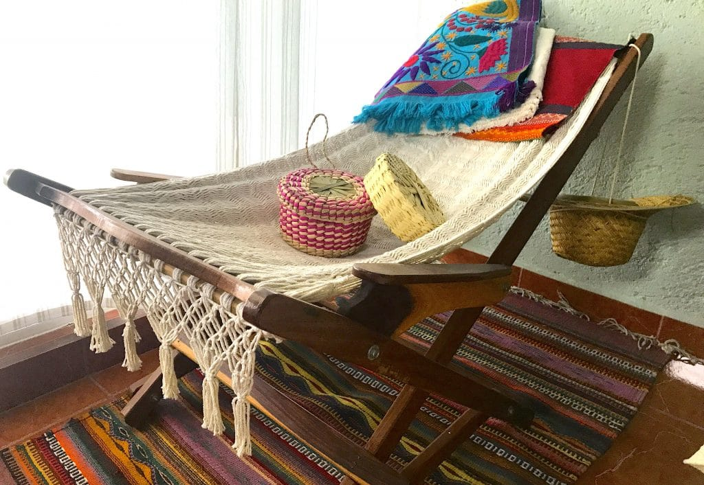 Mexican woven hammock chair, with tortilla baskets and embroidered table runner.