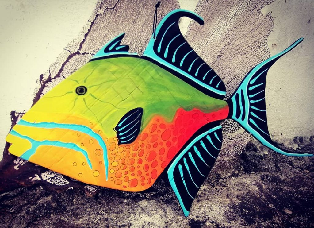 Folk art painting of a brightly colored triggerfish on recycled wood cutout substrate.