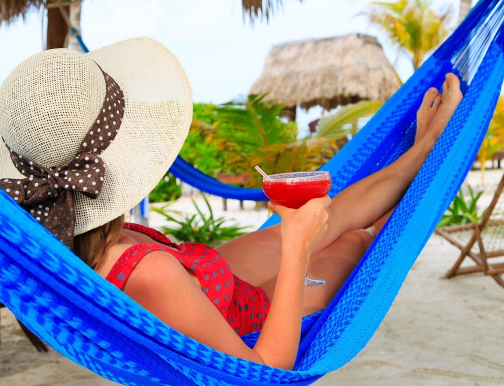 Women in blue hammock with sun hat and tropical cocktail at the beach.