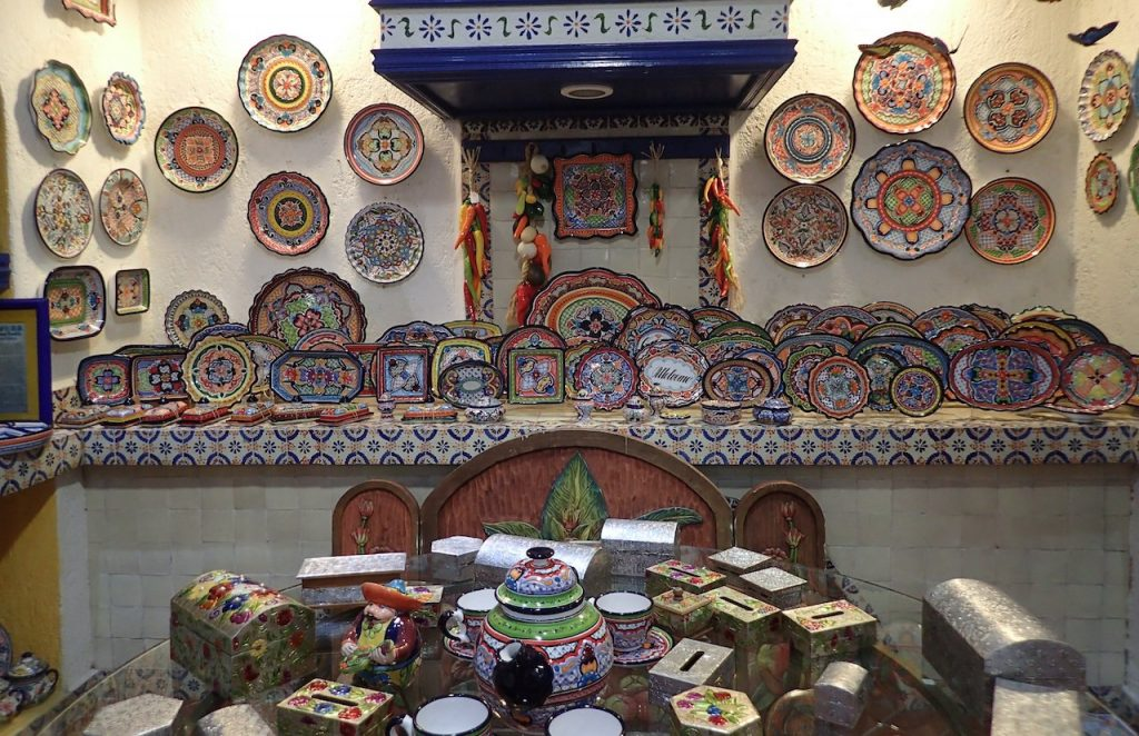 Image of store with nice wide range of Talavera style Mexican painted pottery in all different motifs and colors.