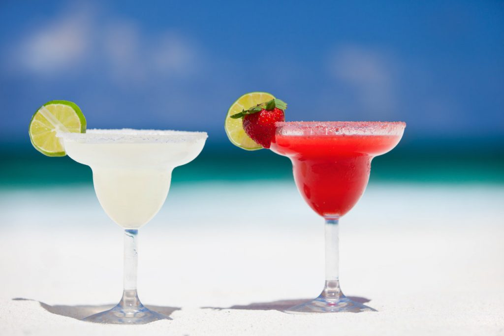 Bright classic margaritas on the sunny, sandy beach as a backdrop.