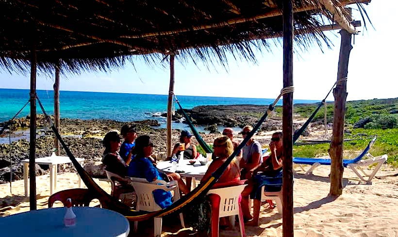 Group at outdoor tables and hammocks on sandy beach of bar along the East Coast of Cozumel.