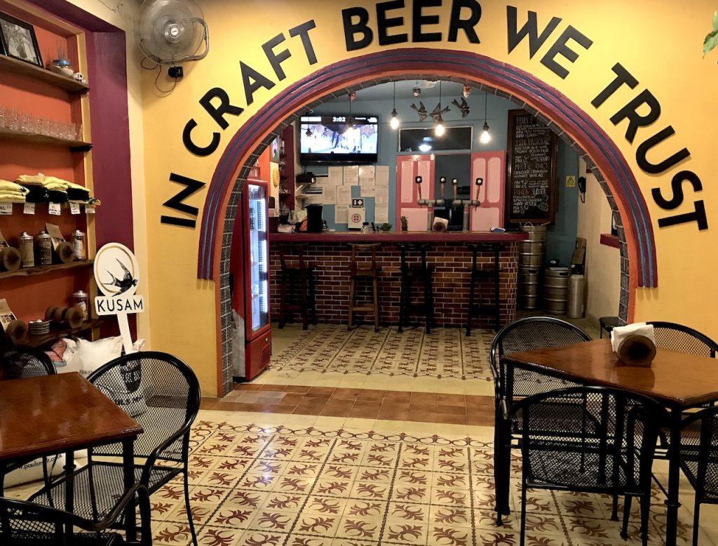 """Fun and funky interior of new Kusam brew bar in Cozumel, with sign saying """"In Craft Beer We Trust."""""""