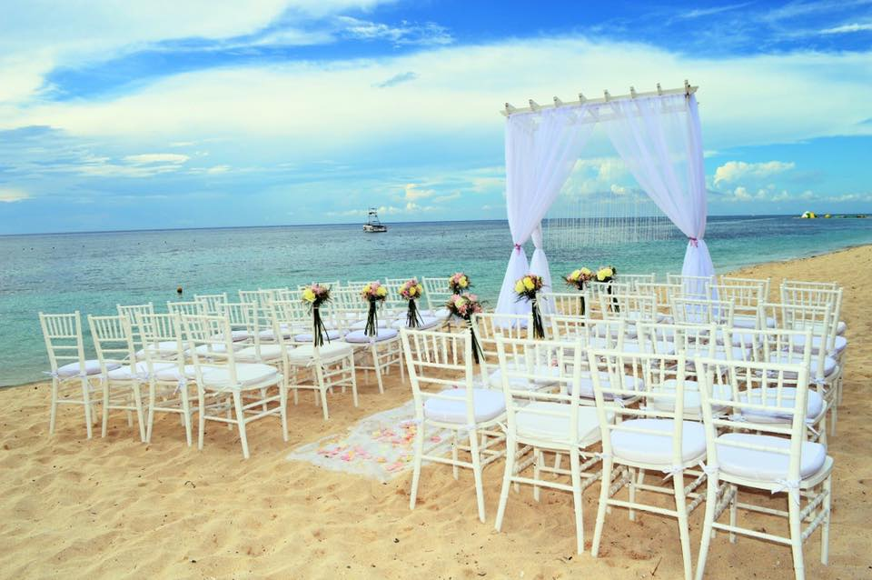 Beach wedding set up on the sand in Cozumel with white chairs, a white fabric 'aisle' and blue ocean background.