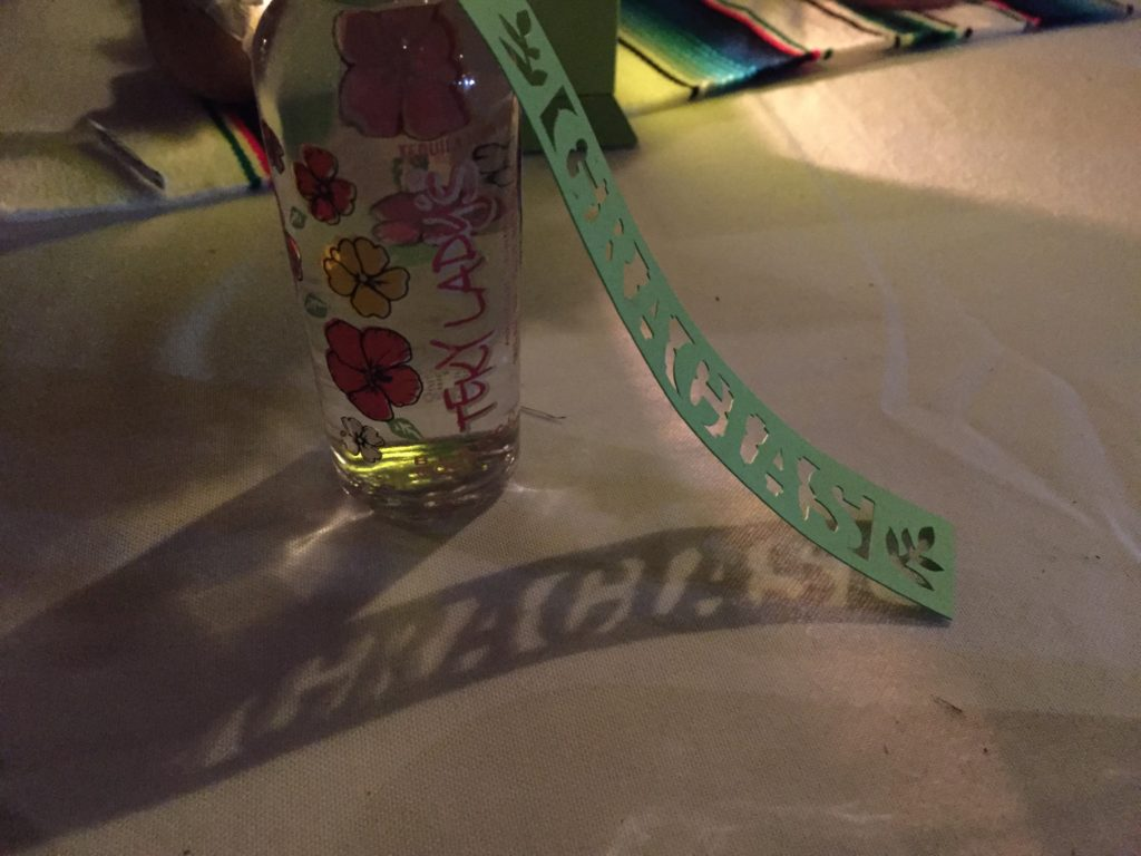 """Wedding reception table with Mexican-style cut paper flags that say """"gracias"""" as party favors."""