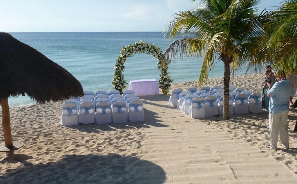 White chairs, a flowered arch, and a raked sand aisle with blue ocean backdrop at a wedding in Cozumel.